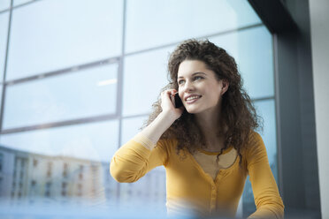 Smiling young woman on the phone at the window - RBF002338