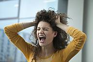 Screaming young woman with hands in hair - RBF002343