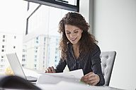 Young woman working at desk in office - RBF002348
