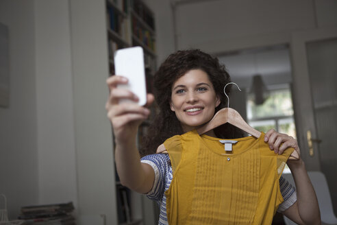 Young woman at home taking a selfie with piece of clothing - RBF002303