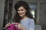 Portrait of young woman at home knitting - RBF002297
