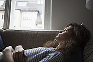 Serious young woman lying on sofa - RBF002261