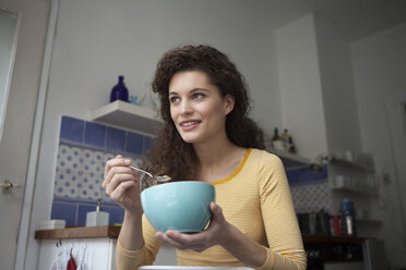 Young woman in kitchen holding cereal bowl - RBF002267