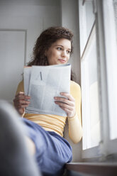 Smiling young woman reading magazine at the window - RBF002276