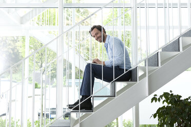 Businessman using laptop on office staircase - MFRF000050