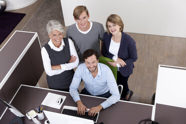 Smiling business team at desk in office - MFRF000016