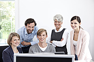 Smiling business team working on computer in office - MFRF000058