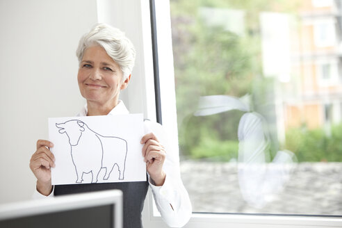 Smiling mature businesswoman holding paper with bull figure - MFRF000010