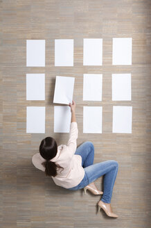 Businesswoman sitting on floor organizing blank sheets of paper - MFRF000043