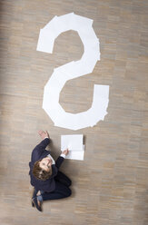 Businesswoman sitting on floor with blank sheets of paper in shape of question mark - MFRF000046