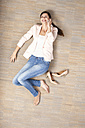 Young woman on cell phone lying on floor - MFRF000059