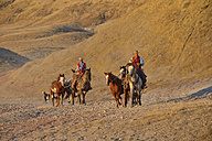 USA, Wyoming, cowboy and cowgirl leading horses in badlands - RUEF001433
