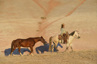 USA, Wyoming, cowgirl with two horses in badlands - RUEF001437