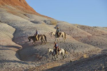 USA, Wyoming, two cowgirls and a cowboy riding in badlands - RUEF001449