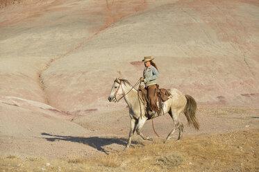 USA, Wyoming, cowgirl riding in badlands - RUEF001451