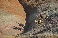 USA, Wyoming, cowgirl and cowboy riding in badlands - RUEF001454