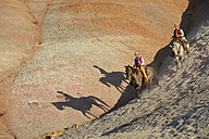 USA, Wyoming, cowgirl and cowboy riding in badlands - RUEF001455
