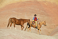 USA, Wyoming, cowboy with two horses in badlands - RUEF001459