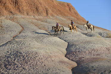USA, Wyoming, two cowgirls and a cowboy riding in badlands - RUEF001464
