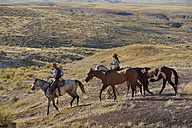USA, Wyoming, cowboy and cowgirl leading horses in badlands - RUEF001469