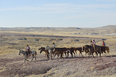 USA, Wyoming, cowboys and cowgirls leading horses in badlands - RUEF001472