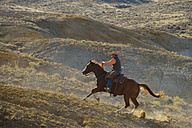 USA, Wyoming, cowboy riding in badlands - RUEF001477