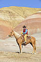USA, Wyoming, cowboy on his horse in badlands - RUEF001483