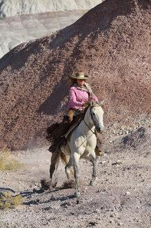 USA, Wyoming, cowgirl riding in badlands - RUEF001501