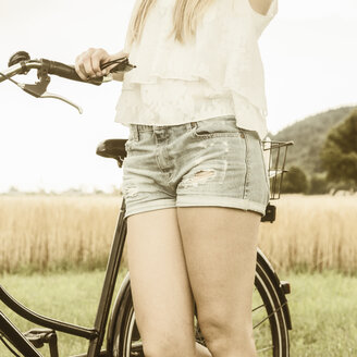 Germany, Young woman wuíth bike wearing hot pants - DRF001253