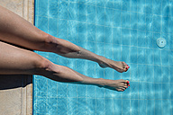 Woman sitting at pool edge with legs in the water - CHPF000015