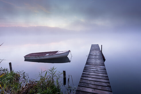 Germany, Wessling, Wesslinger See, boat and wooden boardwalk in the morning mist - MBOF000031