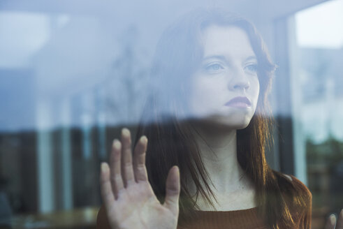 Serious young woman behind windowpane - UUF003222