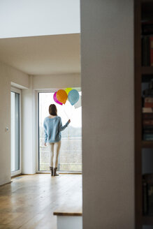 Young woman holding bunch of balloons looking out of window - UUF003234