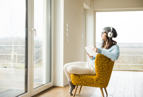 Young woman sitting on chair with digital tablet and headphones - UUF003242