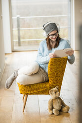 Smiling young woman sitting on chair with digital tablet and headphones - UUF003244
