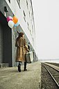 Young woman with suitcase holding bunch of balloons on platform - UUF003264