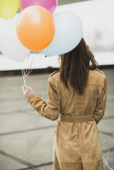Young woman in coat holding bunch of balloons - UUF003267