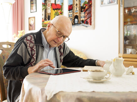 Old man sitting at table using digital tablet - LAF001306