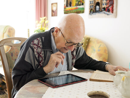 Old man sitting at table using digital tablet - LAF001308