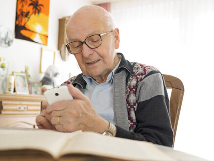 Old man sitting at table using cell phone - LAF001314