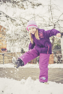 Smiling little girl kicking snow - SARF001319