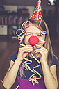 Little girl with clown's nose and cap blowing streamer - SARF001324
