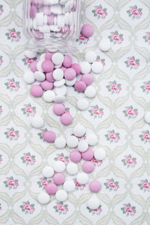 Pink and white chocolate buttons on floral patterned cloth - LVF002739