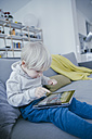 Little boy sitting on the couch playing with digital tablet - MFF001467