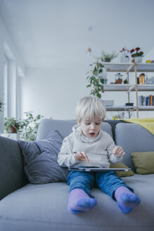 Little boy sitting on the couch playing with digital tablet - MFF001468