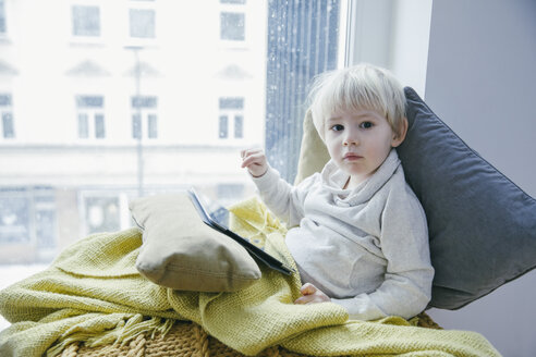 Little boy sitting on the couch playing with digital tablet - MFF001471
