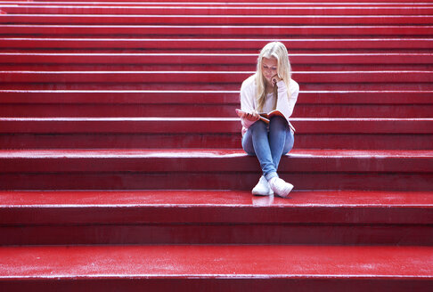 Female teenager sitting on red stairs reading - WWF003756