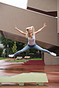 Portrait of blond teenage girl jumping in the air with outstretched arms and legs - WWF003764