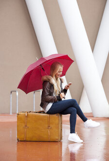 Austria, Thalgau, teenage girl with red umbrella sitting on her suitcase using smartphone - WWF003767