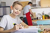 Smiling boy sitting at kitchen table doing his homework - PDF000695
